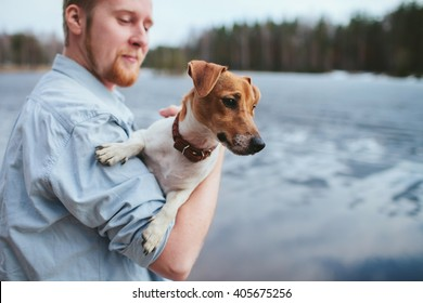 man holds a dog, standing along the shore of the lake and the forest