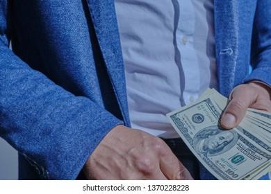 Man holds dollars - Shutterstock ID 1370228228