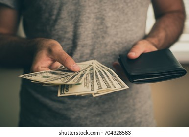 A man holds dollars and black wallet in his hands