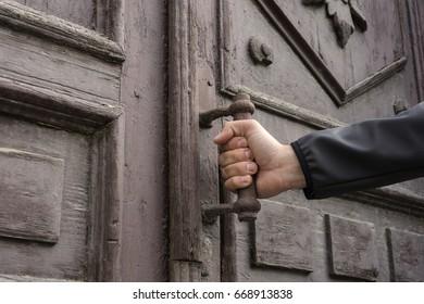 A man holds the door handle to open the door.