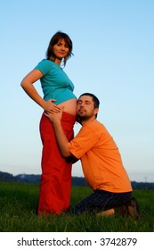 Man holds ear to belly of very pregnant woman