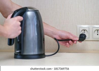 Der Mann hält die elektrische Energie in der Hand und verbindet den Wasserkocher mit der Steckdose