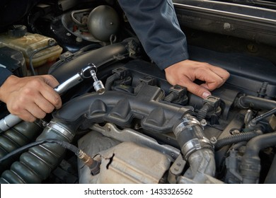A man holds the engine of a car with a torque wrench. Auto repair service and maintenance.
