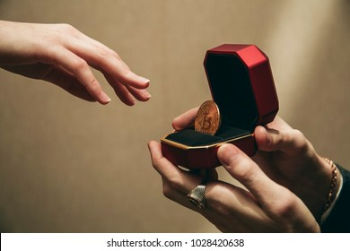 a man holds an expensive ring or jewelry box with bitcoin as if he makes an offer to marry