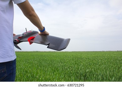 Man holds fixed wings drone while standing in a wheat field, prepares for drone launch and aerial imaging of crops. Right wing visible.