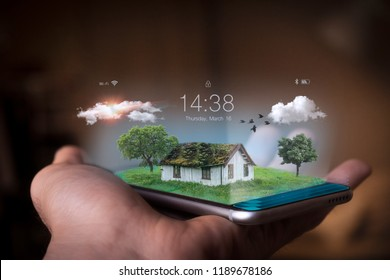A man holds a futuristic phone in his hand, on which he appears the home surrounded by nature and greenery. Concept of: future, respect for the environment and the planet, technology.