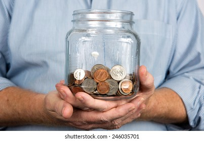 Man holds a glass jar containing United States coins and money.