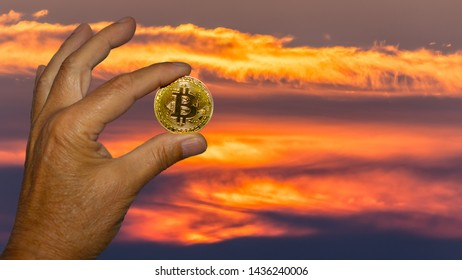A man holds a golden Bitcoin coin in hand in front of a cloud background. The clouds are strongly orange in color and look like a fire burning in the sky.
