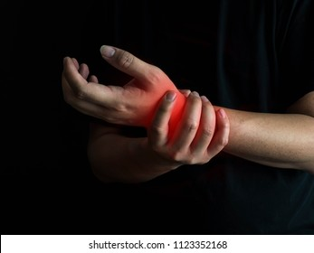 Man holds he wrist hand injury, feeling pain. Health care and medical conept.