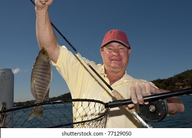 Man holds up his black fish catch
