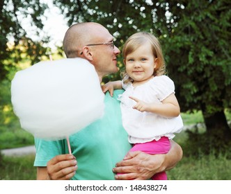 man holds his daughter and cotton candy