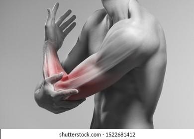 Der Mensch hält seinen Ellbogen an der Hand. Schmerzzone in Arm und Knochen