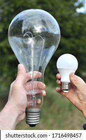 A man holds in his hand a large incandescent lamp and a small energy-saving lamp as a symbol of high energy consumption. Energy saving concept.
