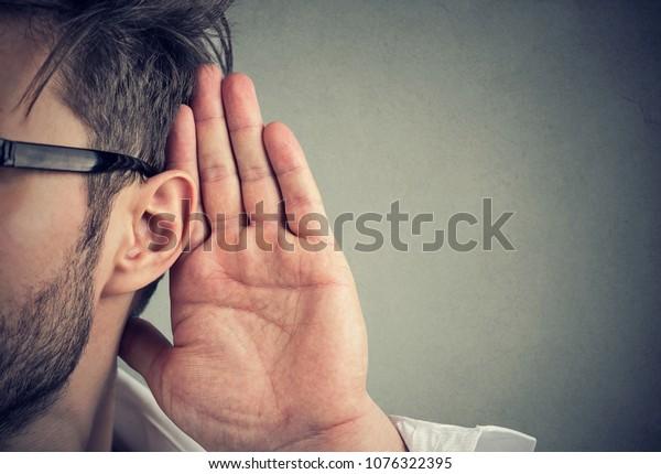 Mann hält seine Hand nahe Ohr und hört aufmerksam einzeln auf grauem Hintergrund