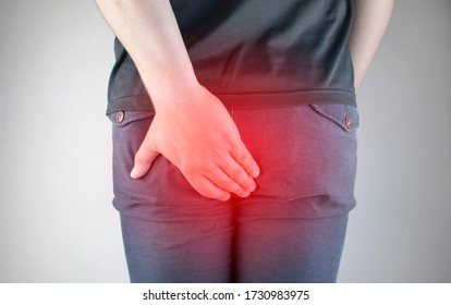 A man holds his hands to the ass feeling pain. Conversion of pain in the rectum, hemorrhoids and pain in the excretory system of the body. Frequent bowel movements.