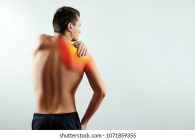 A man holds his hands for a damaged shoulder, a pain in his shoulder highlighted in red. Light background. The concept of medicine.