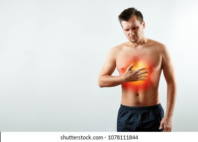 A man holds his hands and region of the heart, chest pain, a pain in the heart highlighted in red, a heart attack. Light background. The concept of medicine, massage, physiotherapy, health.