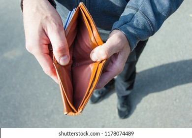 A man holds in his hands and shows a wallet without money