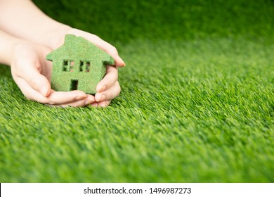 A man holds in his hands a small green eco house. A miniature copy of the house on the palms on a background of grass.