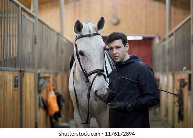 Man holds horse by bridle in riding stables.