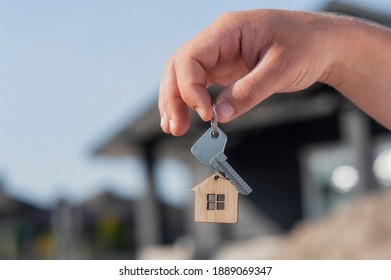 Man holds the keys to the house in his hands against the backdrop of residential buildings. Concept for buying and renting apartments
