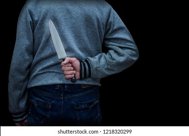 man holds a knife behind his back. concept of danger, hidden threat