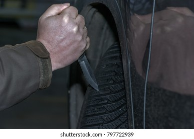 A man holds a knife in his hand and wants to sting with it in a car tire. Slashing into a car tire. Concept: vandalism and crime