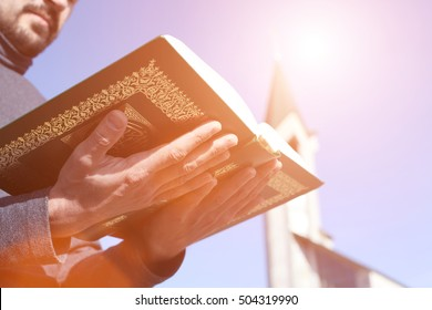 Man holds Koran - holy book of muslims, on blue sky  under the rays of bright sunshine and mosque in blur