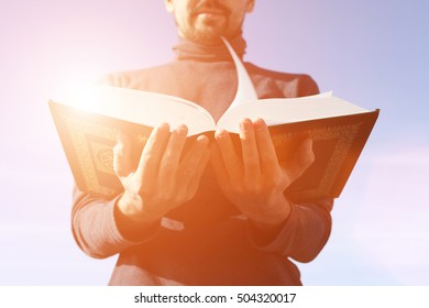 Man holds Koran - holy book of muslims, on blue sky under the rays of bright sunshine