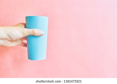 Man holds light blue colorful plastic cup on pink background with copy space for text
