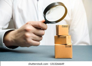 A man holds a magnifying glass above the boxes. Examination of goods for the presence of contraband, prohibited goods, defects. Quality control, authentication. study of consumer sentiment