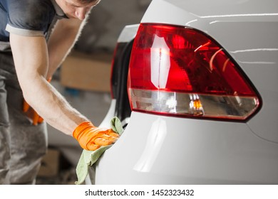 Man holds the microfiber in hand and polishes white vehicle. Car detailing.