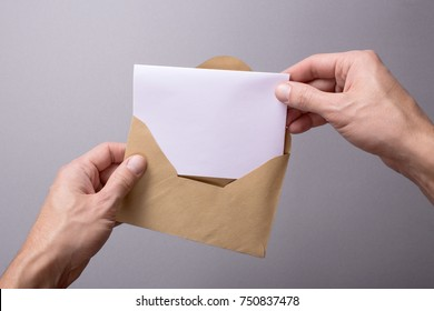 Man holds a mock-up letter or postal card with an envelope on a gray background. A man takes out or puts a letter