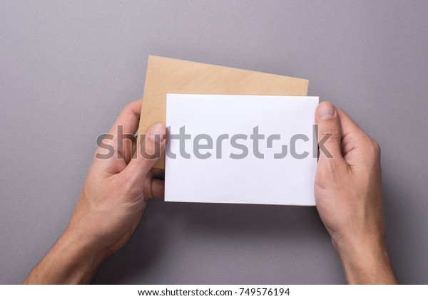 Man holds a mock-up letter or postcard in his hands with envelope on a gray background