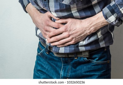 The man holds on to his stomach. Abdominal pain. Diarrhea. Spasm.