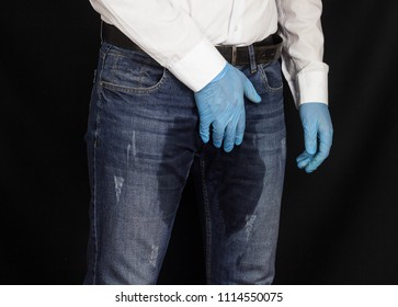 The man holds on to the perineum, the groin in the medical glove, wet pants, prostatitis, male problems