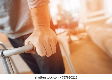 A man holds on to a walker for adults in a nursing home. It's hard for him to go himself. The nurse supports the man.