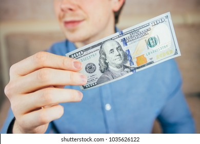 Man holds one new dollar bill