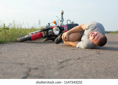 A man holds onto his knee, lying on the asphalt near his motorcycle, the theme of road accidents