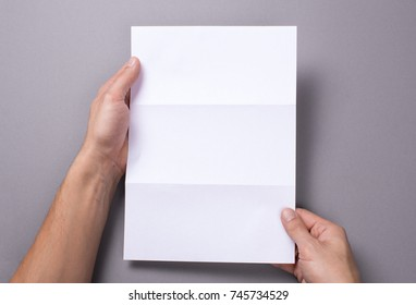 Man holds an open blank letter mock-up and on a gray background