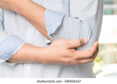 man holds a painful elbow