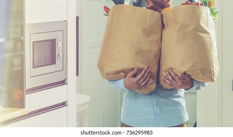 man holds paper bags with food in hands