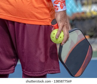 Man holds pickleball paddle and ball in one hand.