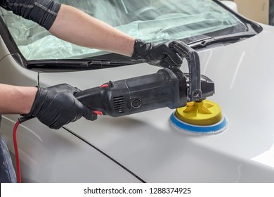 Man holds a polisher in the hand and polishes the car