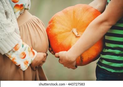 Man holds a pumpkin standing behind a pregnant woman