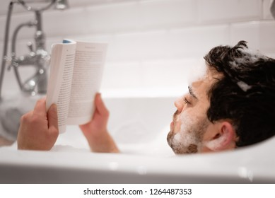 Man holds and reads a book in the tub while covered in bubbles from a bath