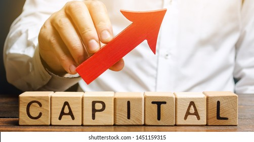 Man holds red arrow up above word Capital. Increase investment and foreign capital in the national economy. Improve business climate and increase attractiveness. Growth and stability of the economy