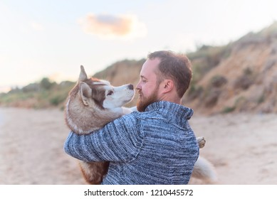 a man holds a redhead husky dog on the background of the sea