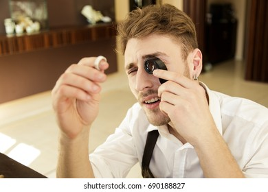A man holds a ring in his hands and looks at it through a magnifying glass. Close-up