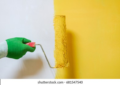 Man holds roller brush with yellow paint over yellow half painted wall